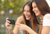 Two women smile while looking at a mobile device.